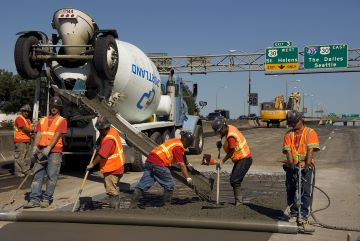 Image of construction workers paving on the highway.